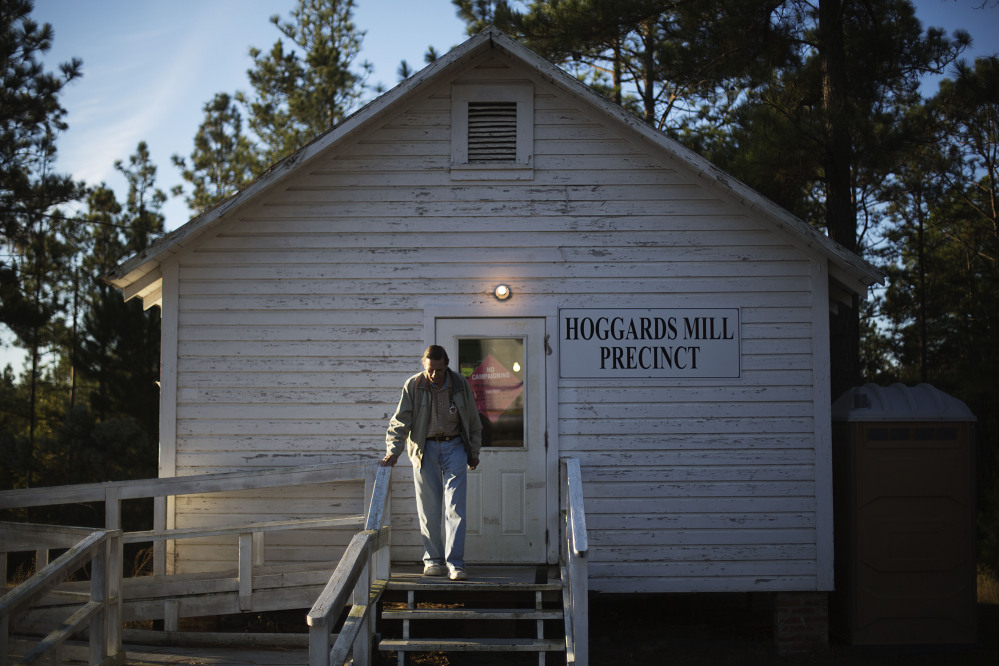 Voter Perry Cross leaves the old Hoggards Mill Courthouse, now a polling site for Baker County, after casting his ballot Tuesday in Newton, Ga.