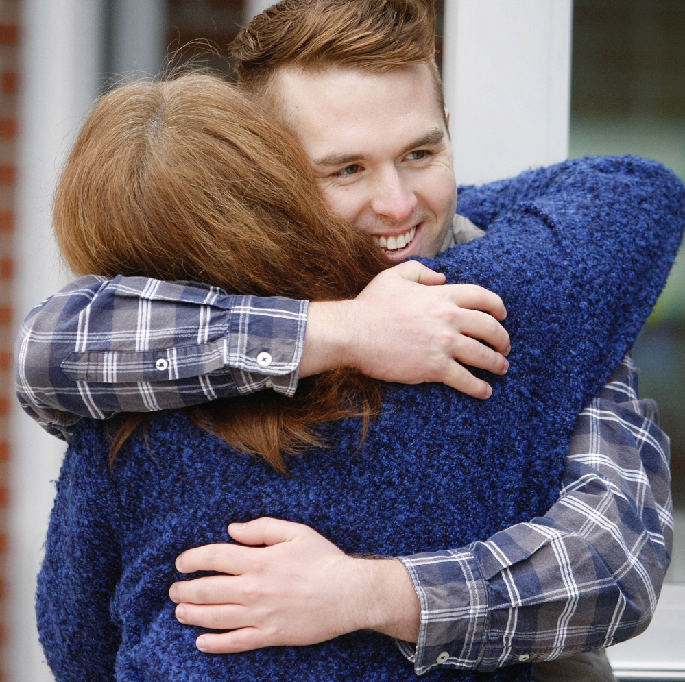 Ryan Fecteau, 22, a Biddeford native, shares a hug with Charlene Dutremble of Biddeford as he greets voters at Biddeford High School on Election Day.