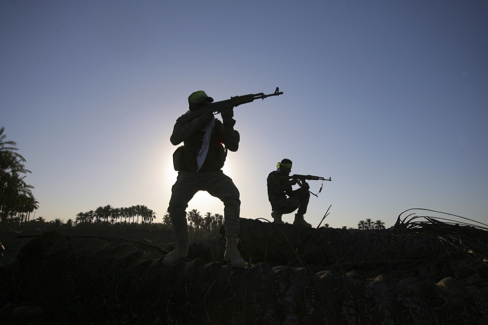 In this Tuesday, Oct . 7,  2014 file photo, Iraqi Shiite militiamen aim their weapons during clashes with militants from the Islamic State group, in Jurf al-Sakhar, about 43 miles (70 kilometers) southwest of Baghdad, Iraq.