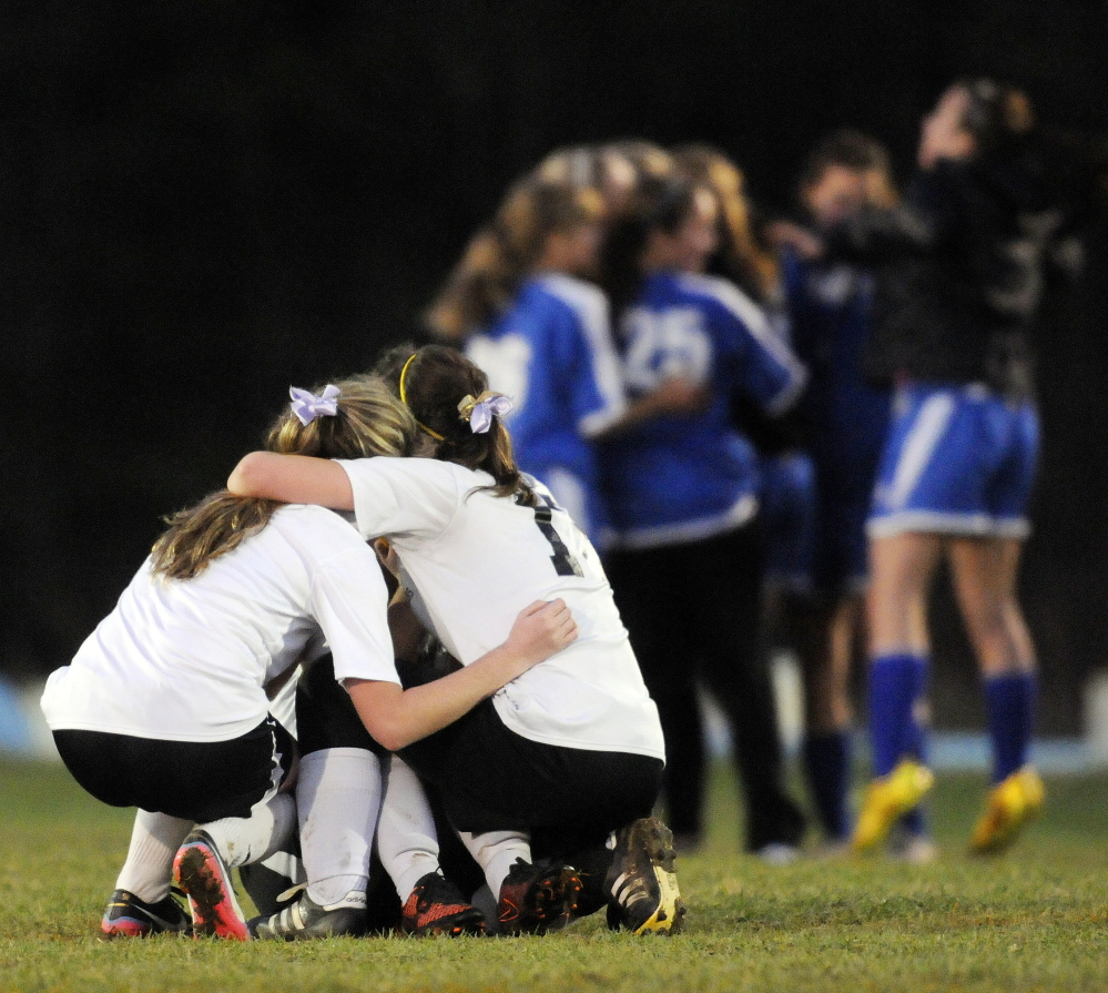 Maranacook players huddle as Sacopee Valley players celebrate their 1-0 victory in the Western C girls' soccer title game Wednesday in Readfield.