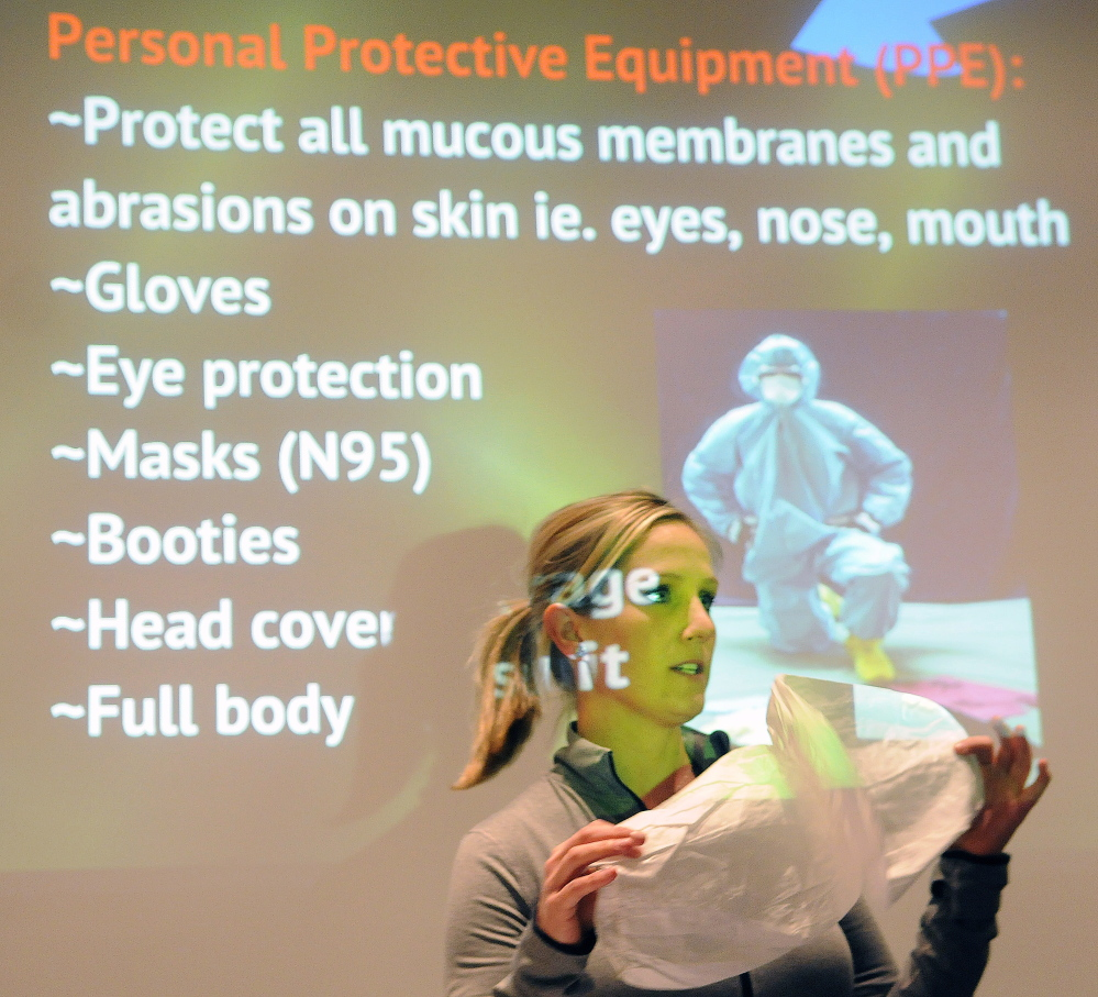 Kerry Gilmore, director of sales for 24-Trauma/Restore, teaches housing authority employees and landlords Wednesday how to protect themselves with booties while cleaning up a biohazard in an apartment during a course at City Center in Augusta.