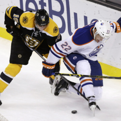 Boston Bruins right wing Reilly Smith and Edmonton Oilers defenseman Keith Aulie go for the puck during the third period of Thursday night's game in Boston. The Bruins defeated the Oilers, 5-2.