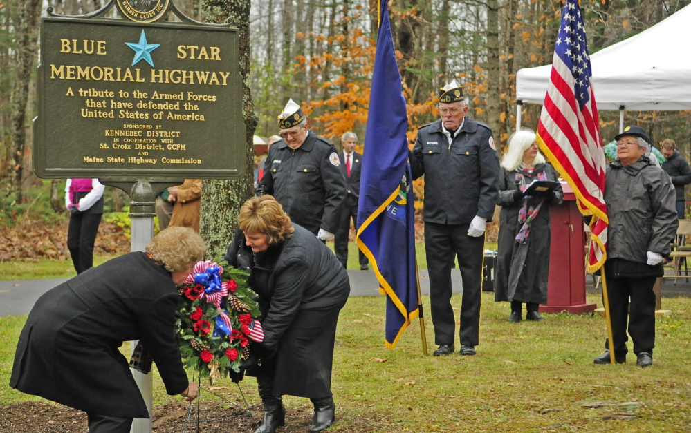Debra Burnham, of the Garden Club Federation of Maine, left, and first lady Ann LePage assist in the dedication of the new Blue Star Memorial Highway marker on Friday in Augusta.