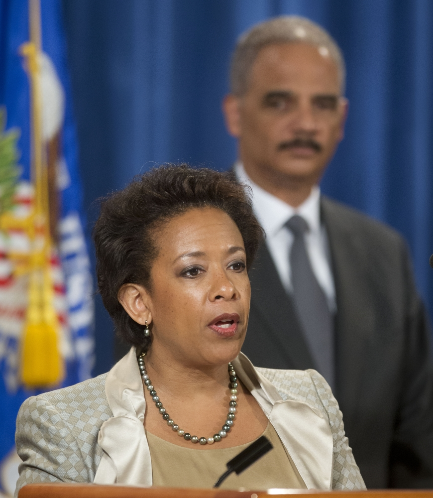 Attorney General Eric Holder listens to Loretta Lynch during a July 28 news conference in Washington.