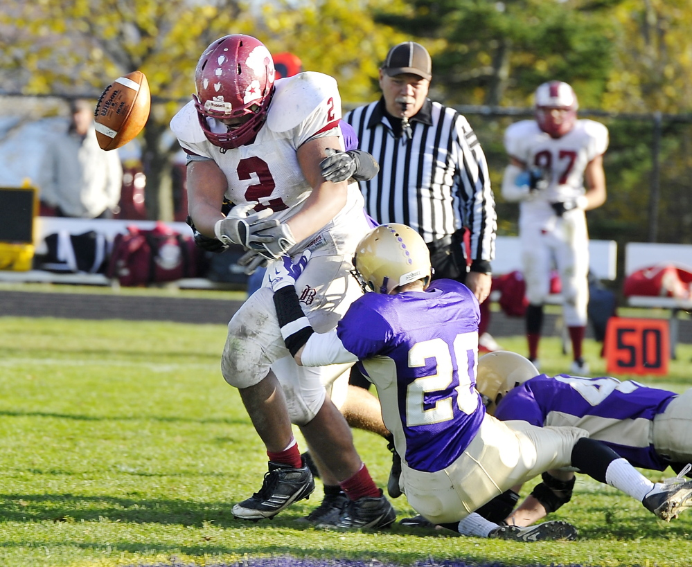 Dan Baker, 20, and the Cheverus defense force a fumble by Bangor's Langston Hamer-Nagle during the Stags' 35-6 win. Cheverus forced three fumbles and intercepted a pass on its way to the victory and a berth in the Eastern A regional final.