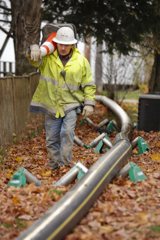 Francis Poulin of CCB Construction Services in Westbrook walks Friday along a natural gas pipe that's ready to be pulled underground along Main Street in Yarmouth. CCB is doing installation work for Summit Natural Gas of Maine.