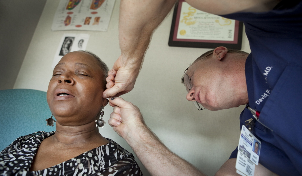 Joslyn Shipman, an Army veteran with PTSD, reacts to having small acupuncture needles put in her ear at a Richmond, Va., VA hospital that is piloting alternative therapies. The VA health care system scandal was a product of understaffing and undertraining, not low quality of care.