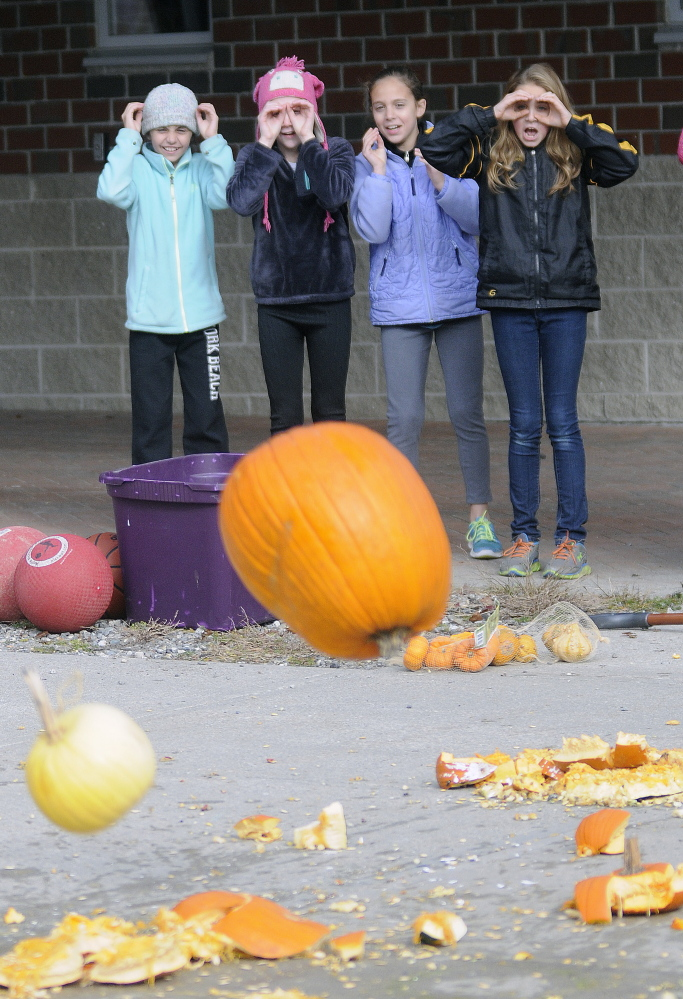 Maranacook Community Middle School students watch pumpkins hit the pavement Monday at the school in Readfield after being dropped from a Central Maine Power bucket truck. The students were learning about Newton's laws of physics for a class.