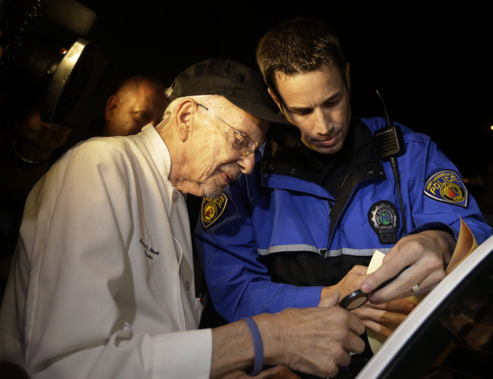 Ninety-year-old homeless advocate Arnold Abbott is fingerprinted by a police officer last week for violating an ordinance limiting where the homeless can be fed.