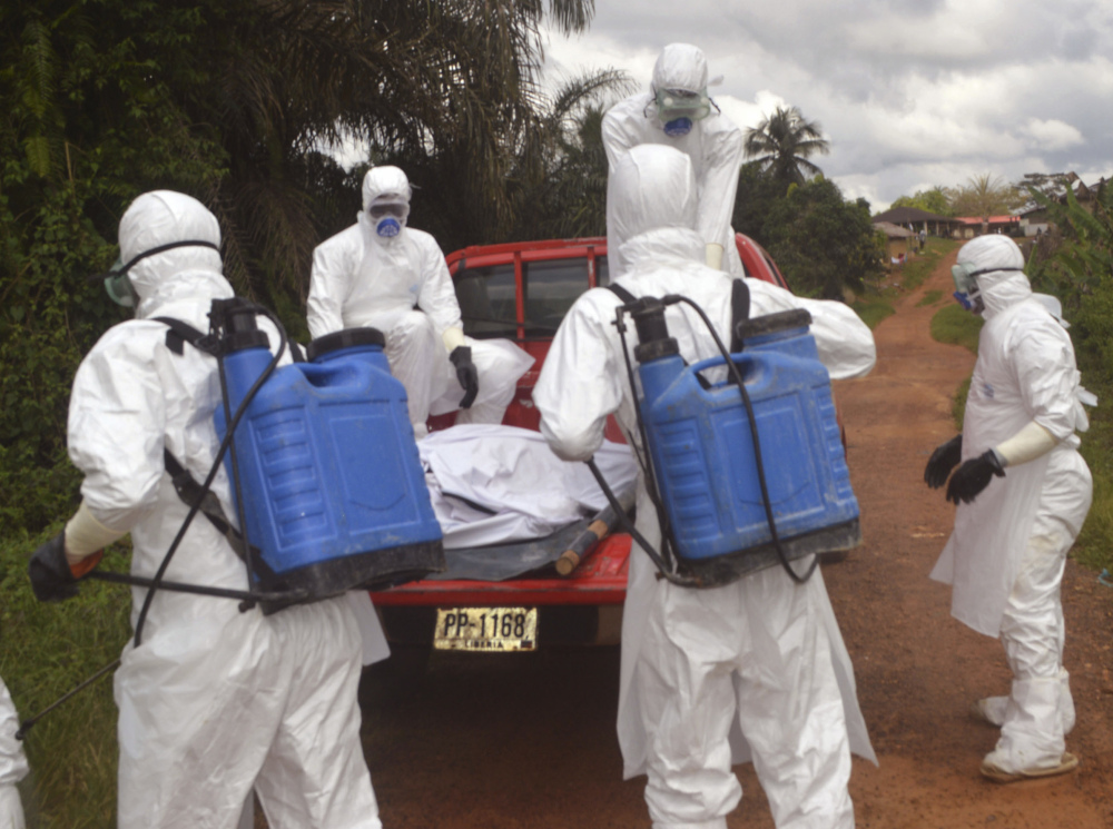 Health care workers load the body of a dead woman suspected of dying from Ebola, onto a truck in Jenewonde near the Liberia-Sierra Leone border, where medical care is now largely dependent on volunteers with Doctors Without Borders.