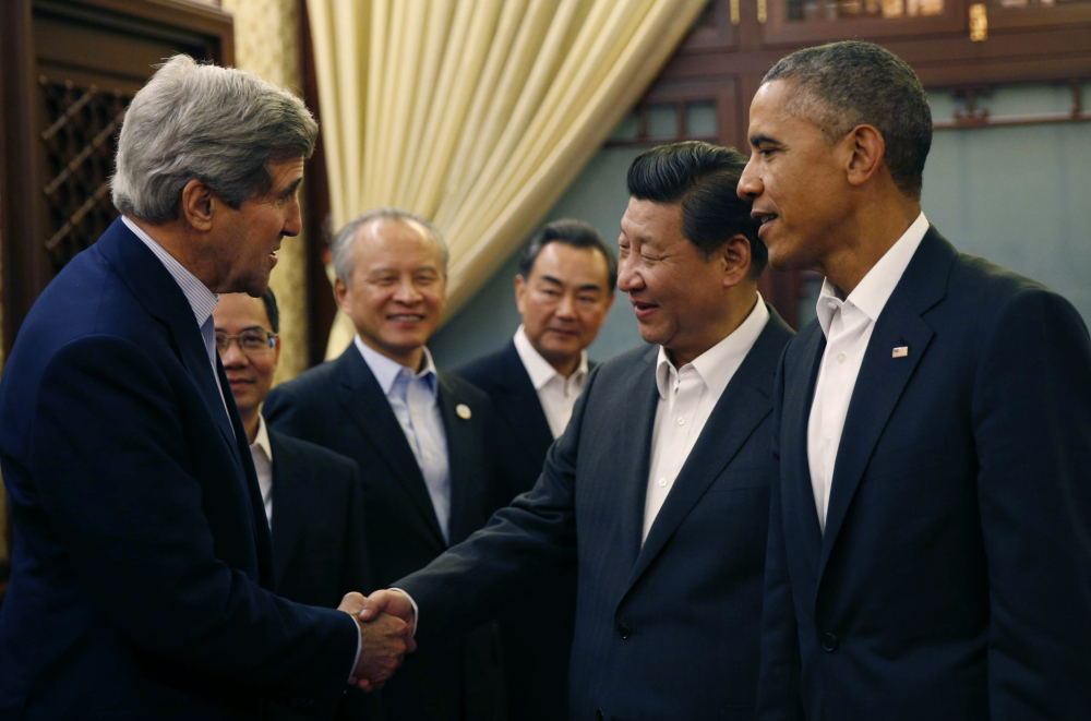 U.S. President Barack Obama, right, looks on as China's President Xi Jinping, second right, shakes hands with U.S. Secretary of State John Kerry, left, at the start of a meeting after participating in the Asia Pacific Economic Cooperation (APEC) summit at the Zhongnanhai leadership compound in Beijing Tuesday. Obama has also met with Russian President Vladimir Putin while at the summit.