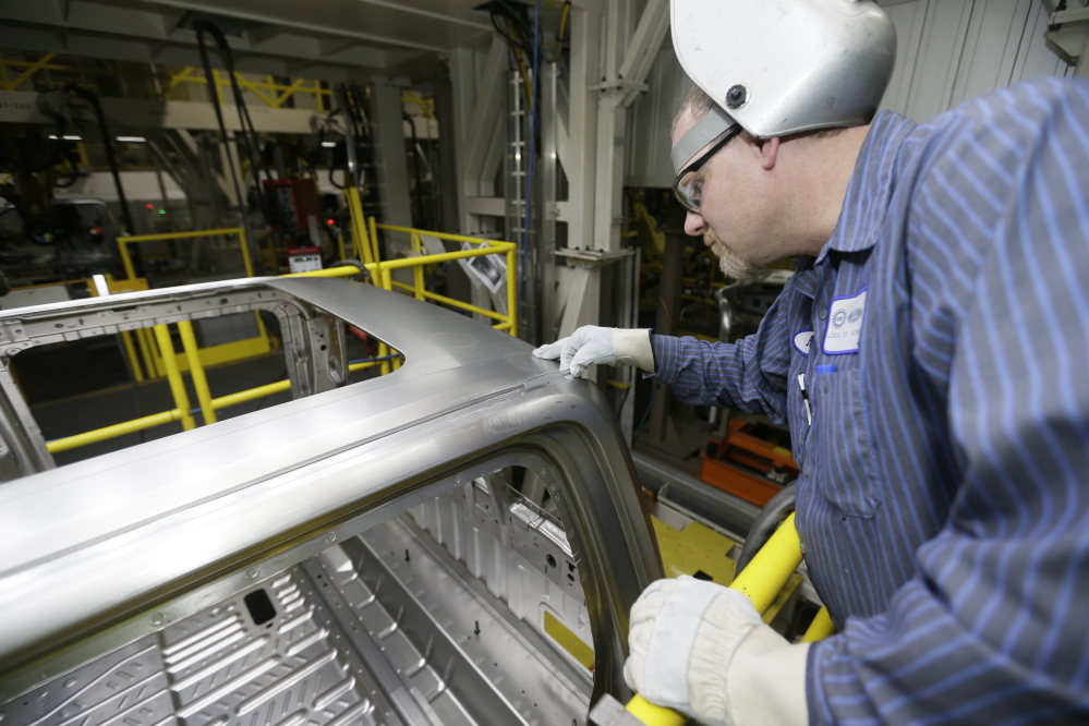 Ron Hudgin measures the roof line of the F-150 truck at the Rouge Truck Plant in Dearborn, Mich. It's the automaker's biggest bet in decades: an aluminum-sided F-150 that could set a new industry standard - or cost the company its pickup truck crown.