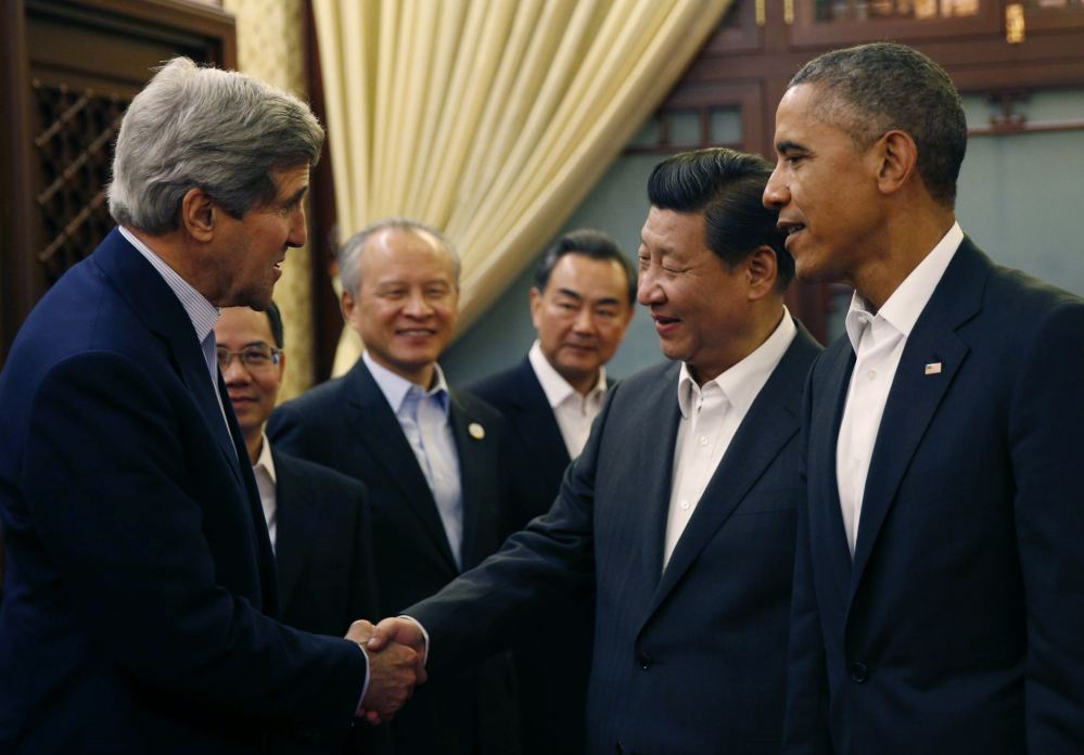 President Obama looks on as China's President Xi Jinping shakes hands with U.S. Secretary of State John Kerry during a two-day Asia Pacific Economic Cooperation summit in Huairou, China.