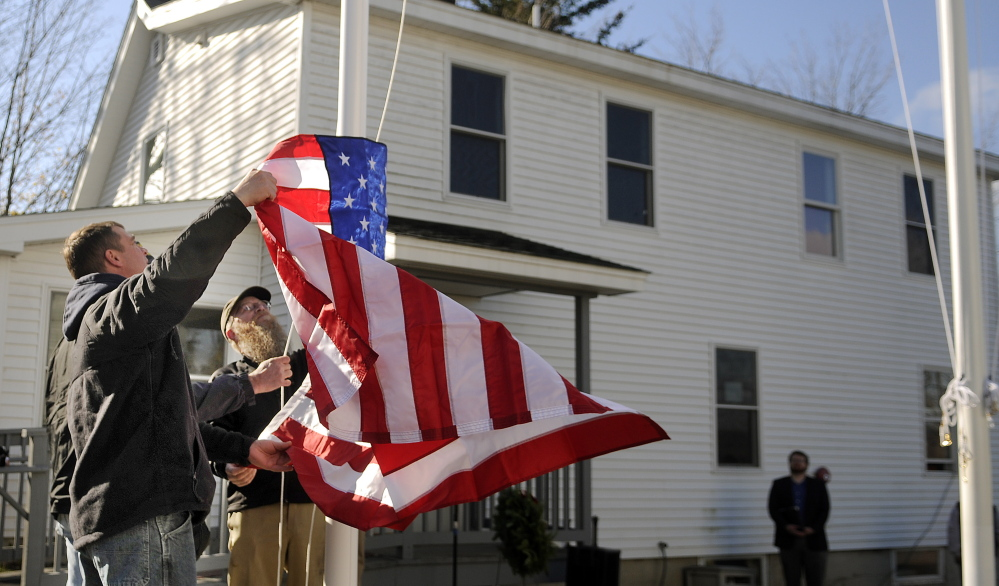Veterans raise the colors Tuesday on the new flagpoles that were dedicated at the Bread of Life Ministries Veterans Shelter in Augusta. Shelter residents helped erect the poles and raised the flags.