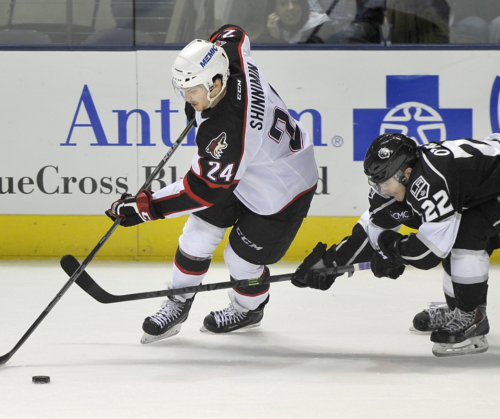 Brendan Shinnimin of the Portland Pirates controls the puck while skating in front of Brian O'Neill of the Manchester Monarchs. Portland lost to the Monarchs for the second time this season.