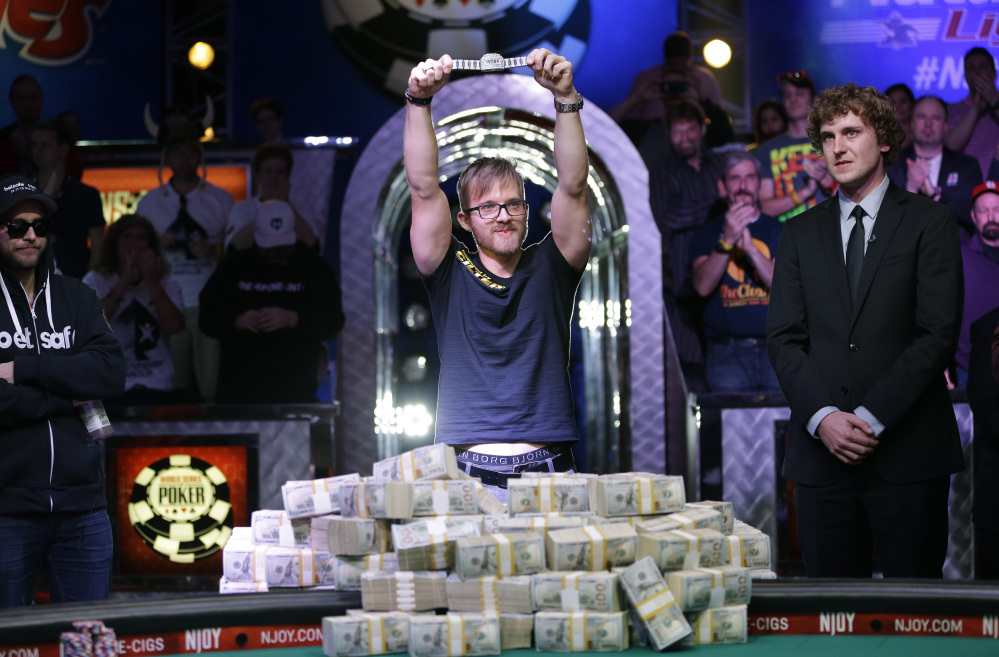 Martin Jacobson holds up the World Series of Poker main event bracelet after winning the tournament and its $10 million prize, Tuesday in Las Vegas.