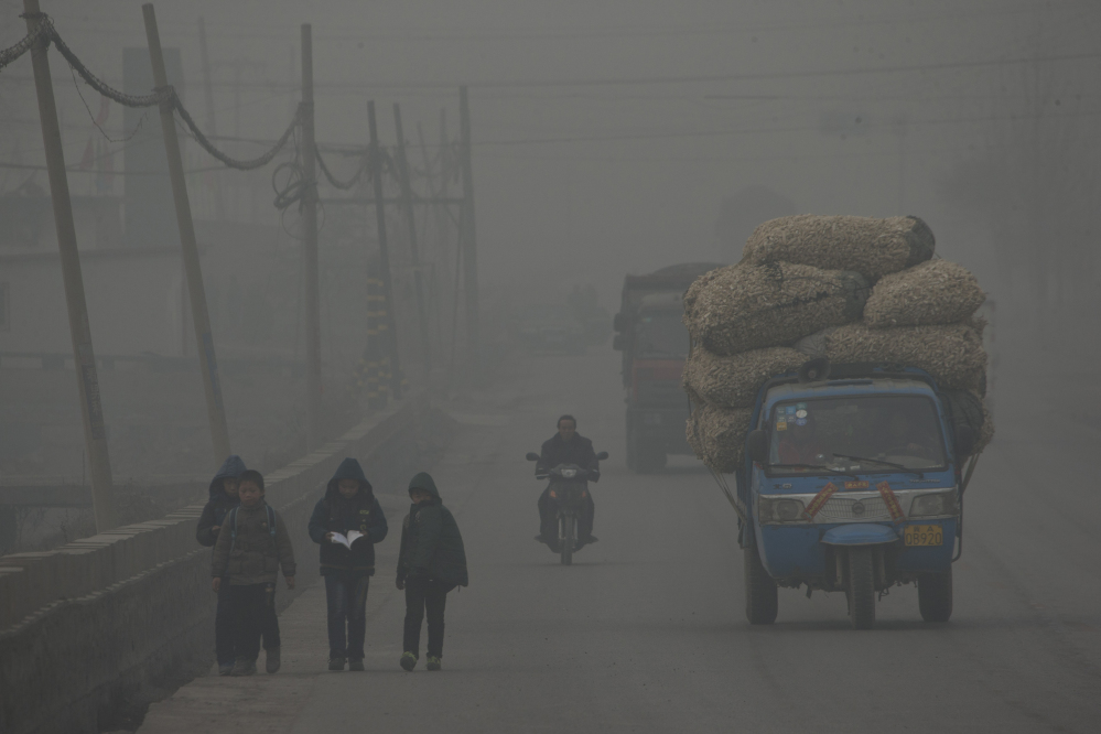 Children walk home after school on a severely polluted day in Shijiazhuang, in northern China's Hebei province. A groundbreaking agreement struck Wednesday by the United States and China puts the world's two worst polluters on a faster track to curbing the heat-trapping gases blamed for global warming.