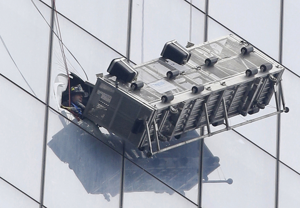 A firefighter looks out an opening cut into a window at 1 World Trade Center after rescuing two workers from their collapsed scaffolding Wednesday. The two window washers were trapped for more than an hour on the south side of the 1,776-foot, 104-story building.
