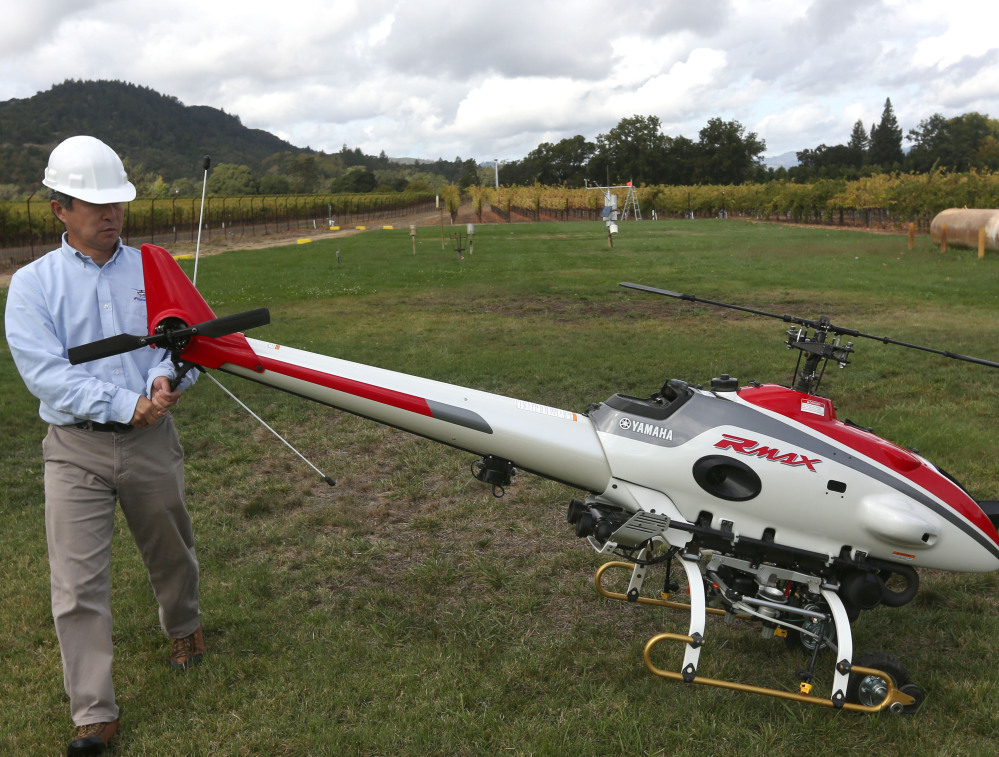 A worker puts an RMax unmanned helicopter into position for a demonstration flight. The FAA's near-total ban on drone use has been largely ignored.