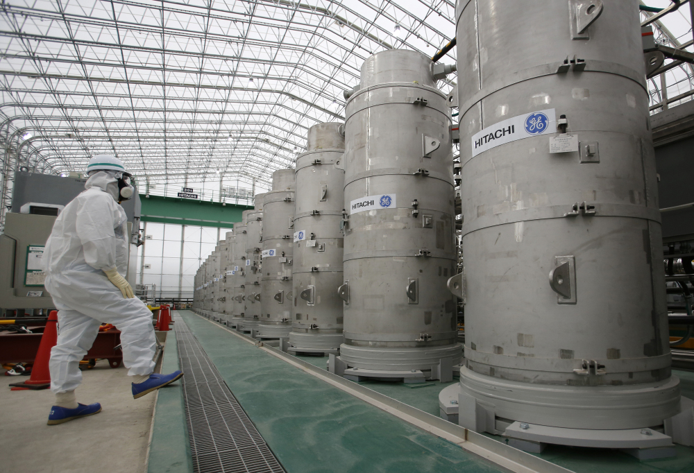 A visitor wearing protective gear looks at a system designed to remove radioactive elements from water at the Fukushima Dai-ichi nuclear power plant in northeastern Japan.