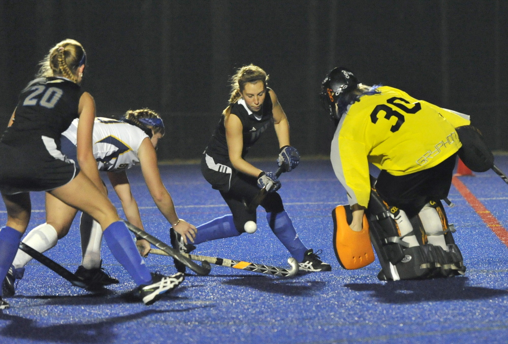 Alex Staples of the University of New England has her stick ready for a rebound Wednesday night as Simmons goalie Brianna Rastello prepares for a save during UNE's 2-0 victory. UNE plays Middlebury next.