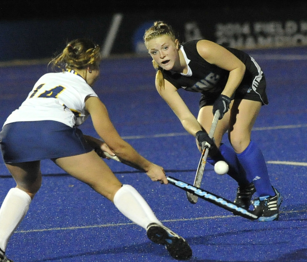 Alyssa Kowal of the University of New England hits the ball past Marra Wagner of Simmons during UNE's 2-0 victory Wednesday night in NCAA field hockey.