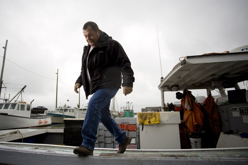 Chief Frederick Moore III of the Pleasant Point reservation steps off his fishing boat in Eastport.