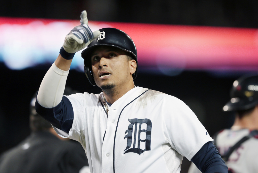 Detroit Tigers designated hitter Victor Martinez points to the stands after his solo home run against the Cleveland Indians in Detroit on Sept. 13. A person with knowledge of the deal says the Tigers have agreed to a $68 million, four-year contract with Martinez.  The Associated Press