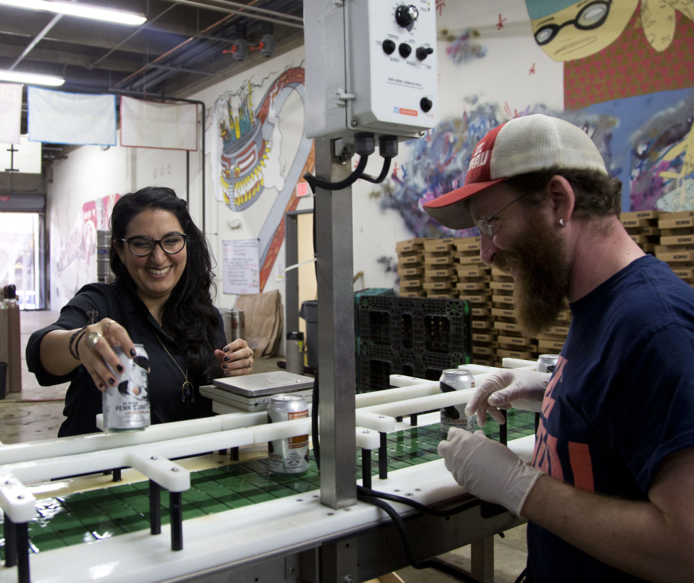 Employee Jason Budman works with Mari Rodela, chief community and culture officer for DC Brau Brewing Co. in Washington. The microbrewery lined up more than 50 insurance options for its workers through the small-business exchange.