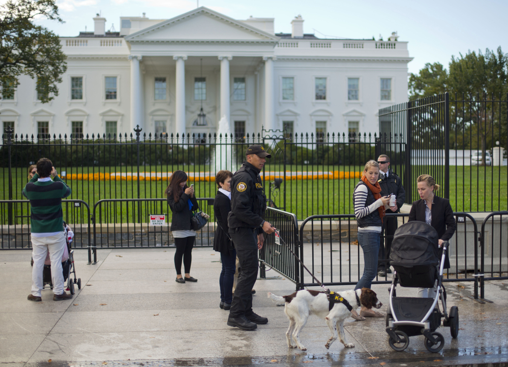 A Secret Service police officer dog patrol walks on the sidewalk in front of the White House in Washington last month.