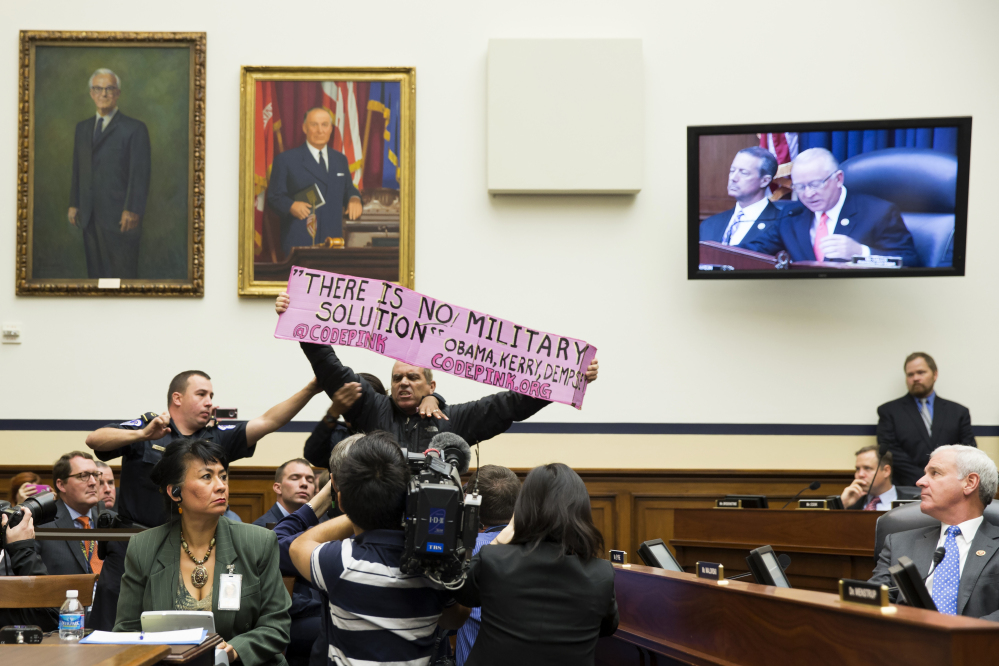 A CodePink protester is removed by police on Capitol Hill in Washington after interrupting a House Armed Services Committee hearing Thursday with Defense Secretary Chuck Hagel, and Joint Chiefs Chairman Gen. Martin Dempsey on the Islamic State .