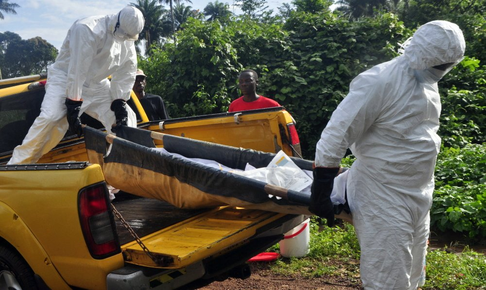 Health workers unload the body of a man suspected of contracting the Ebola virus near Monrovia, Liberia, last month. Comparing patients receiving drug therapy to patients who are not is a long-established testing technique considered the gold standard of medical research.