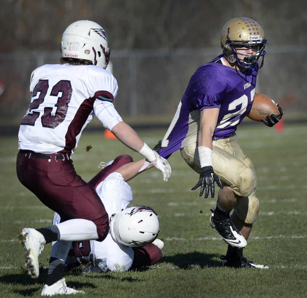 Joe Fitzpatrick, who gained 177 yards for Cheverus while dealing with a pulled muscle, attempts to break away from Griffin Jacobson of Windham as Tanner Laberge moves in during Windham's overtime victory Saturday.