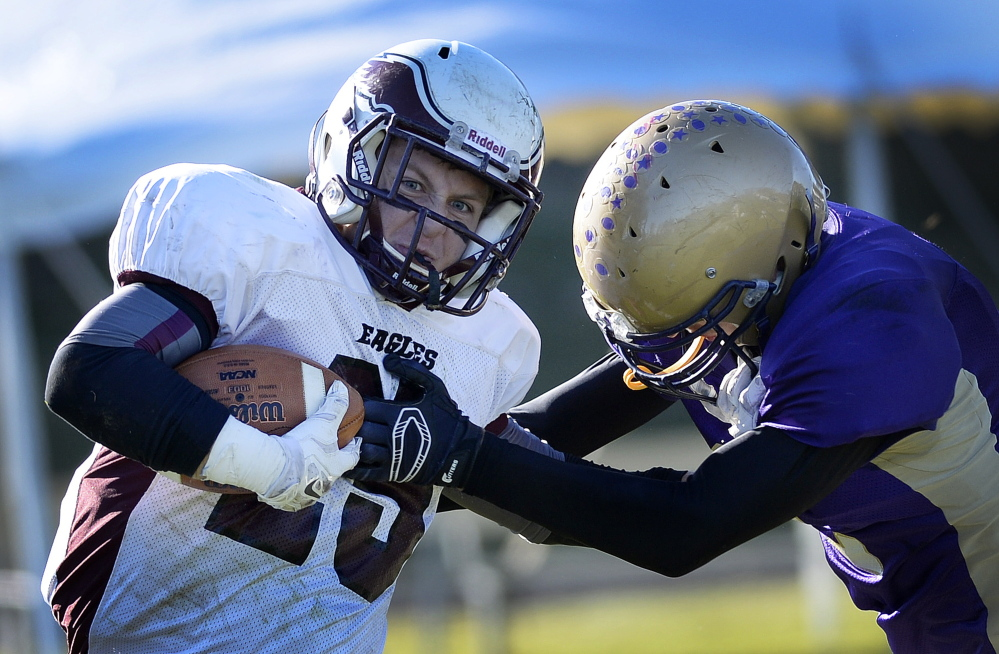 Dylan Koza of Windham attempts to break away from a Cheverus defender and gain extra yardage Saturday during their Eastern Class A championship game at Cheverus High. Windham rallied from a 14-3 deficit in the fourth quarter for a 21-20 overtime victory.
