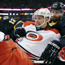Carolina Hurricanes' Zach Boychuk, second from right, and Boston Bruins' Dennis Seidenberg battle for the puck during the first period Saturday at Boston.