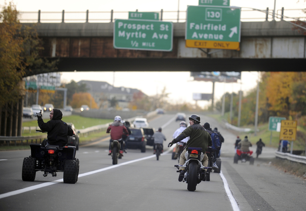 ATV and dirt bike riders cruise illegally on a city street in Bridgeport, Conn. Groups of such riders gather through word of mouth or social media to ride through cities, pulling stunts and evading police.