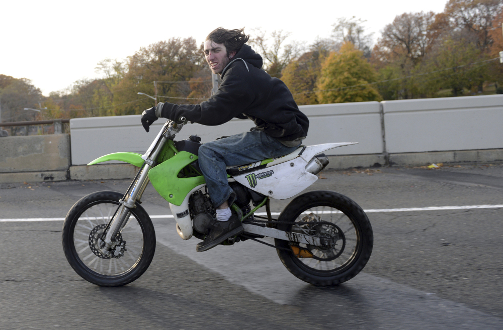 An unidentified man illegally rides a dirt bike on a city street. Two of the bikers from this Nov. 8 ride were caught after wrecking their rides, and police were able to arrest seven others after their ride was over.