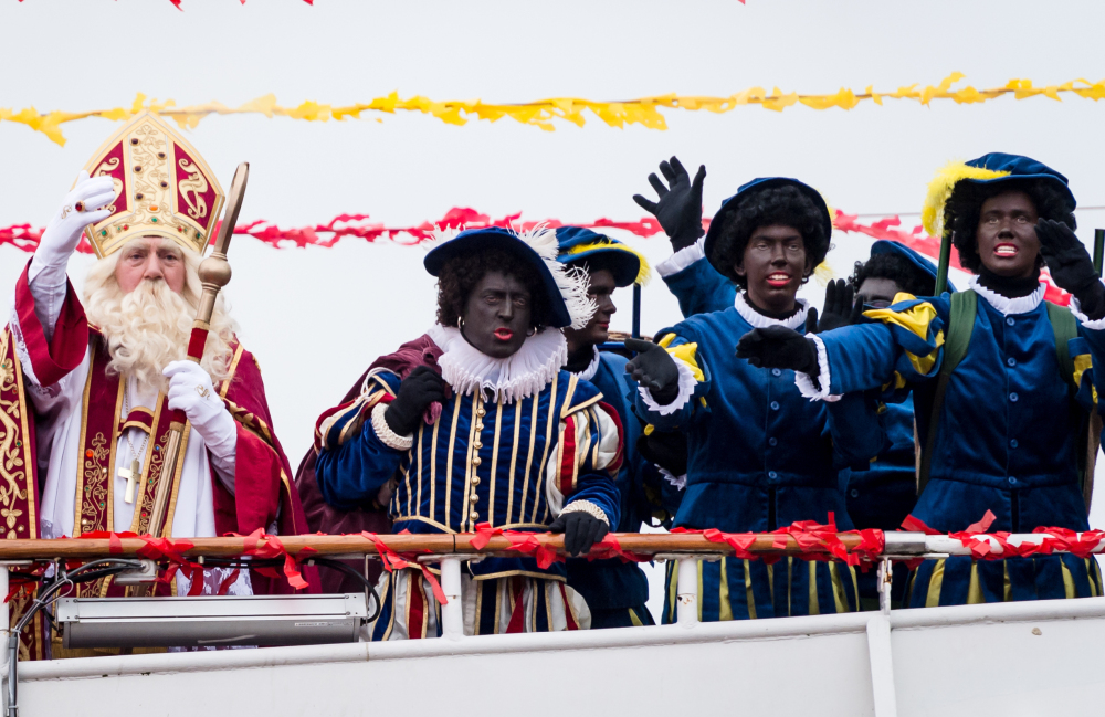 Actors dressed as Saint Nicholas, left, and Black Pete arrive on a boat in Antwerp, Belgium, on Saturday. Some say Black Pete is a racist caricature.