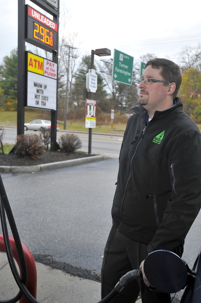 Limerick resident Josh Bisson fills his tank with gas in Auburn, where he works, for $2.96 a gallon. As oil prices plummet, he has gone from spending $65 twice a week to top off his Subaru to $55 for each fill-up, saving $20 a week.