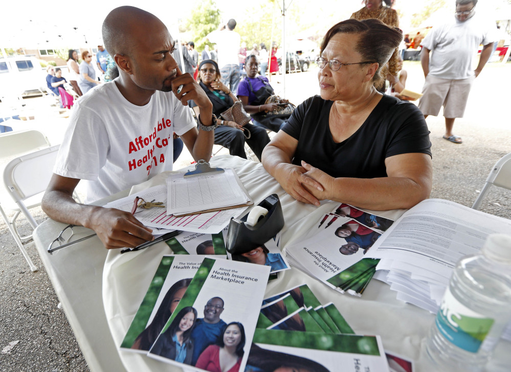 """Josephine White, right, explains her medical needs to Wilbert Jones, a certified application counselor at the """"Get Covered Mississippi"""" event at the Jackson-Hinds Comprehensive Health Center in Jackson, Miss., in 2013. Open enrollment began Saturday for people shopping online for health insurance. About 60,000 Mississippi residents bought coverage during the first period of open enrollment a year ago."""