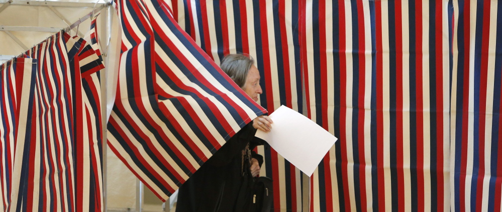 Ballots in hand, a woman leaves a voting booth at Kennebunk Town Hall on Nov. 4. A group behind subtly threatening mailers that went out to some Maine voters used personal data from Maine's Central Voter Registration database, which contains detailed information about members of the state's electorate, including party affiliation and when they voted. Gregory Rec/Staff Photographer