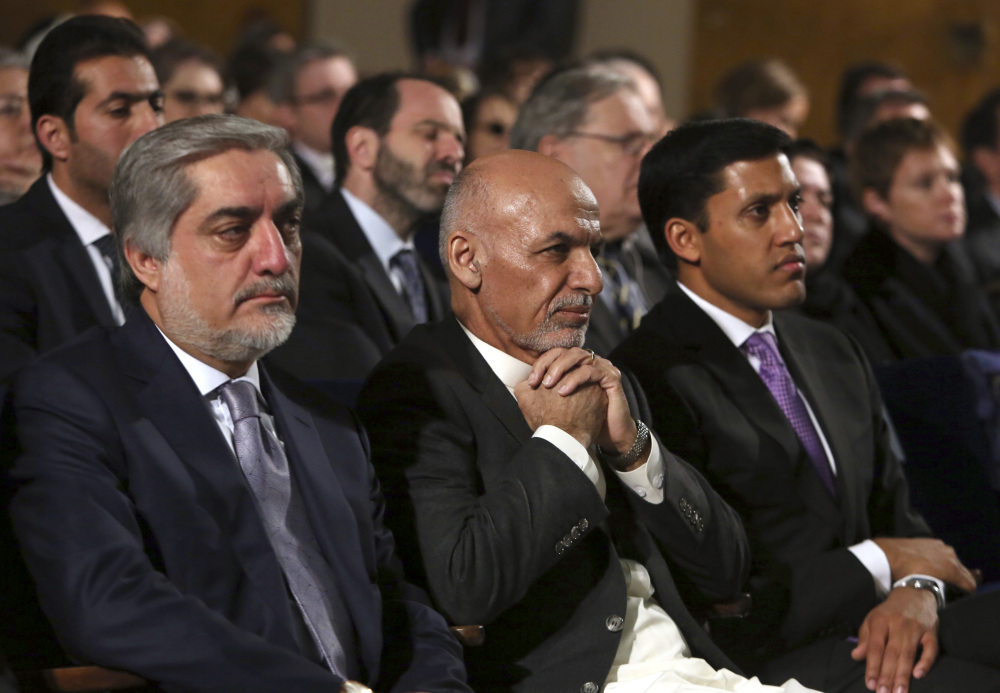 Afghan President Ashraf Ghani, center, sits next to chief executive Abdullah Abdullah, left, his former rival while attending an event in Kabul, Afghanistan, this month. Ghani and Abdullah are restructuring the country's long-troubled government.