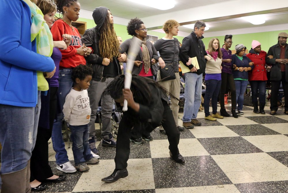 The Rev. Osagyefo Sekou, a pastor from the First Baptist Church in Jamaica Plain, Mass., demonstrates, at a protest training session in St. Louis, Mo., last week, how police might try to intimidate protesters by beating on the ground with their clubs.