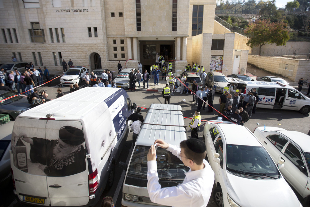 An ultra-Orthodox Jewish youth takes a picture at the scene of a shooting attack in a synagogue in Jerusalem.