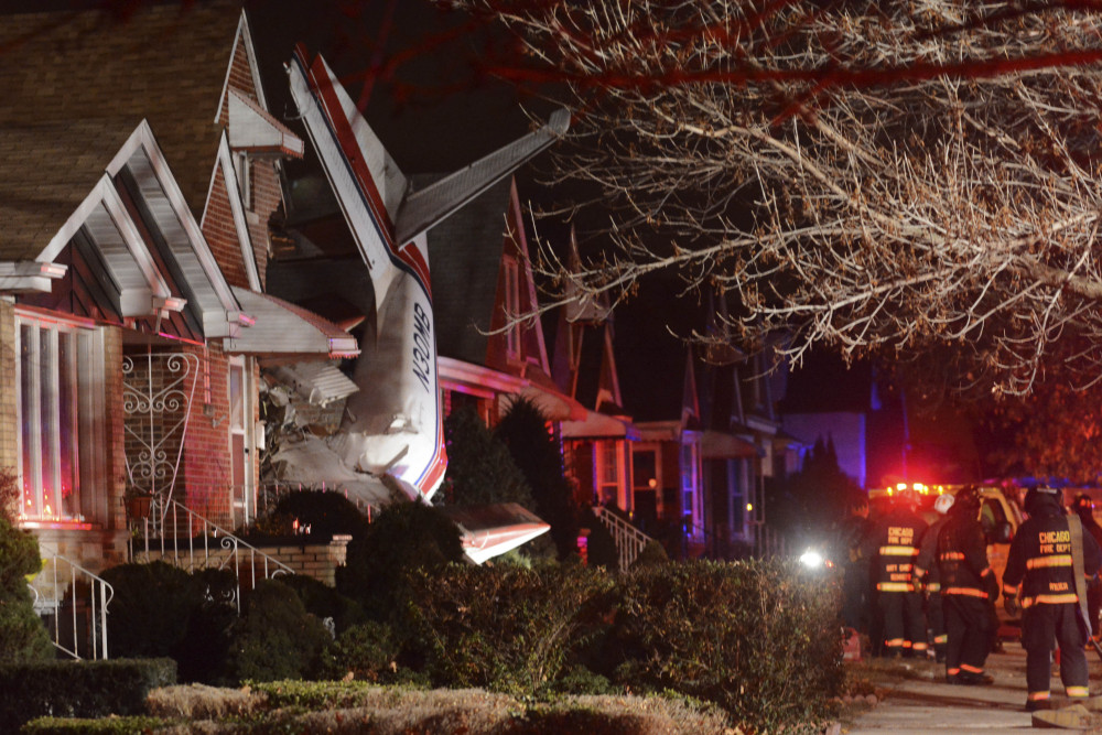 A small twin-engine cargo plane is seen after it crashed into a home on Chicago's southwest side early Tuesday shortly after taking off from Midway International Airport.