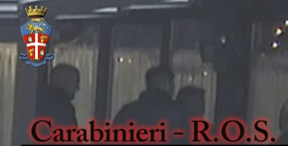 In this photo taken from a video provided by the Italian Carabinieri, or paramilitary police, people identified by police as Italian crime sindicate 'ndrangheta' members perform a ritual swearing-in ceremony.