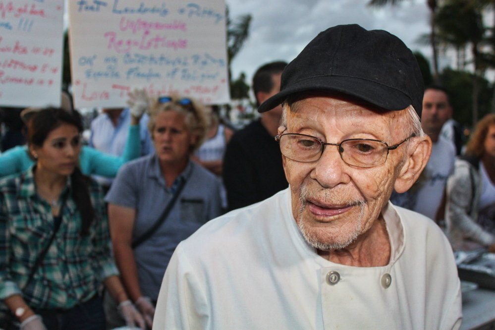 Arnold Abbott, left, is a 90-year-old World War II veteran who heads the Love Thy Neighbor organization in Fort Lauderdale, Fla. His group of volunteers helps to feed homeless people in the city by hosting meals, top photo, outside in a local park. A new ordinance was passed to restrict outdoor feedings – a move the city's mayor hoped would persuade Abbott to find an indoor venue for his charitable services.
