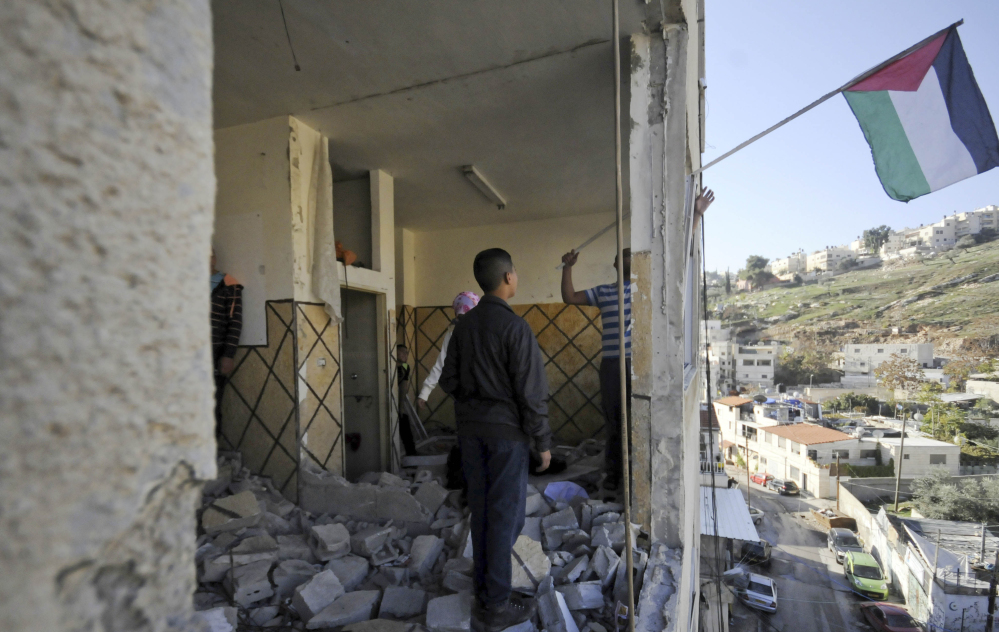 Palestinians hang a flag in an apartment in Jerusalem on Wednesday. Israeli officials demolished the home in response to a deadly attack on a Jerusalem train station last month.