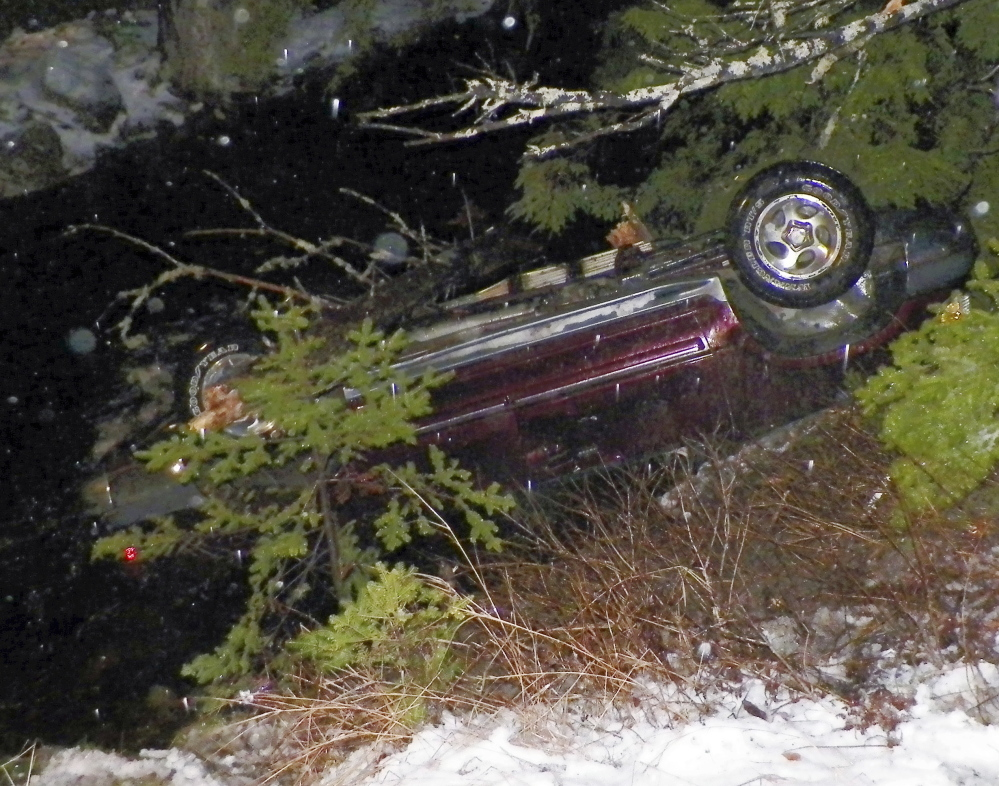 An SUV rests along Route 6 in Kossuth Township. An infant was taken to Eastern Maine Medical Center, and two other passengers were treated and released from a hospital.