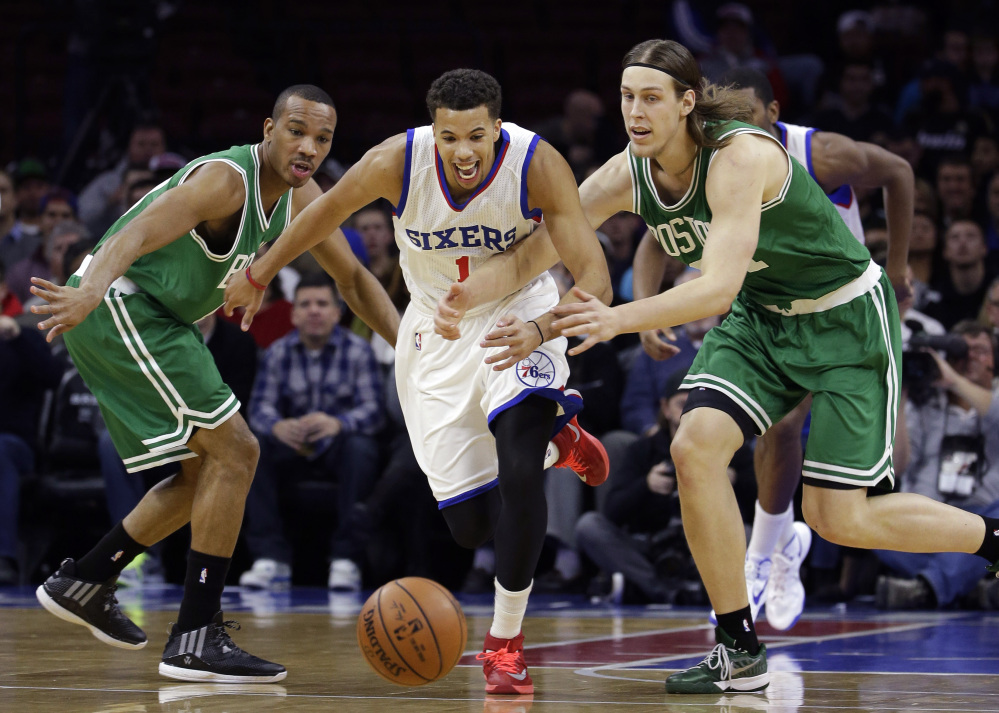 The Philadelphia 76ers' Michael Carter-Williams, center, chases after a loose ball between Boston Celtics Avery Bradley, left, and Kelly Olynyk during the first half of Wednesday night's game in Philadelphia. Boston improved to 4-6 with the win.